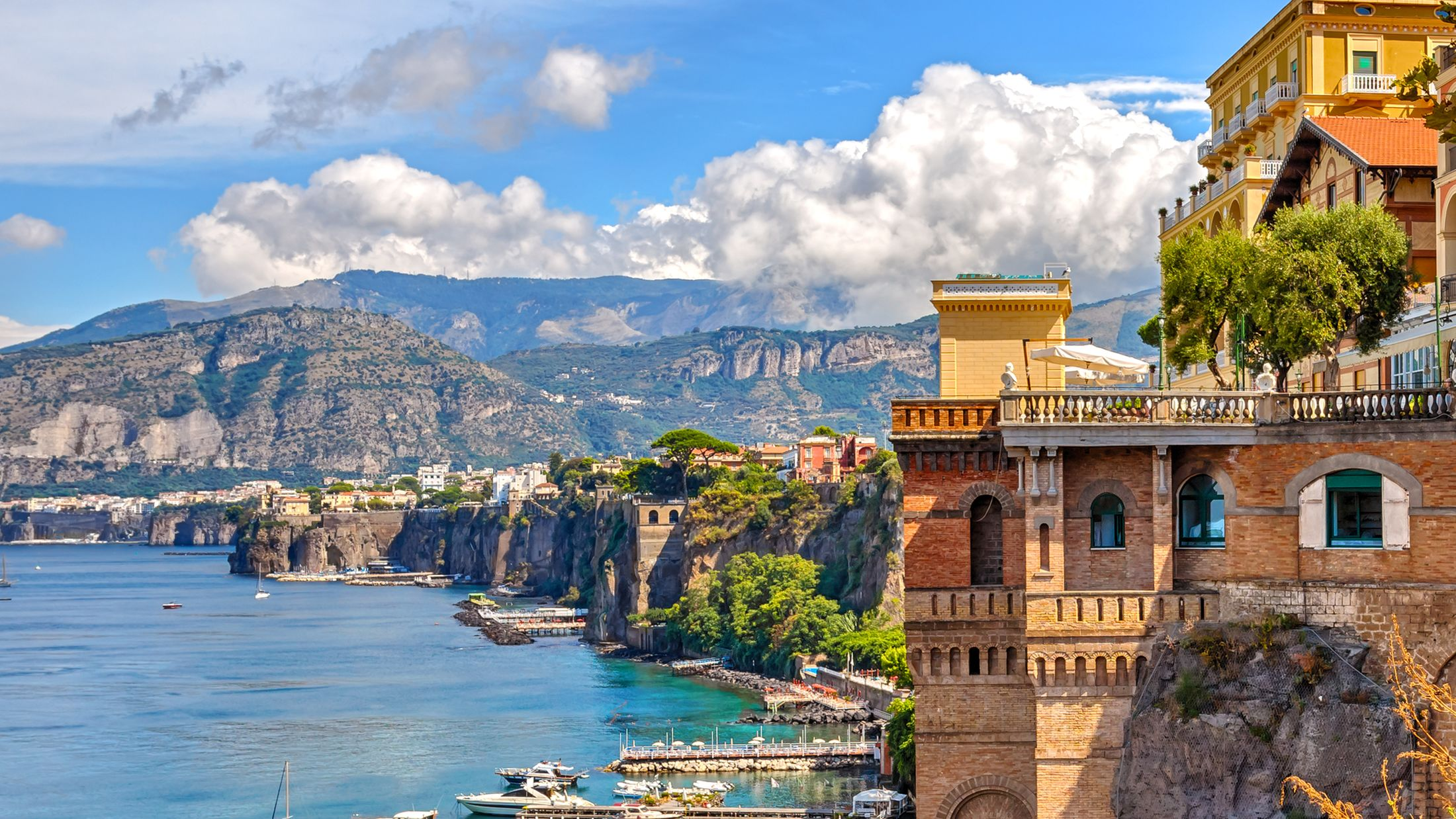 A view of the coast of Sorrento, with a classic building on the right, and mountains in the background